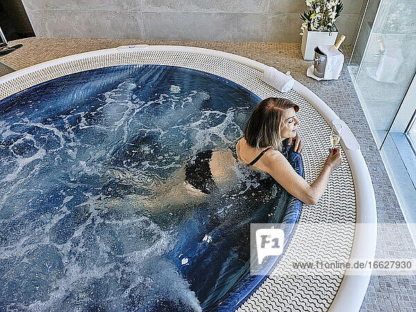 High angle view of senior woman holding wine while leaning in swimming pool