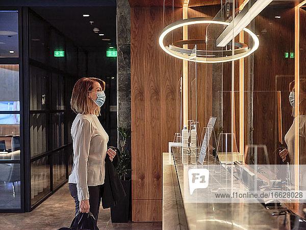 Ältere Frau betrachtet Glasmaterial  während sie in der Hotellobby steht Ältere Frau betrachtet Glasmaterial, während sie in der Hotellobby steht