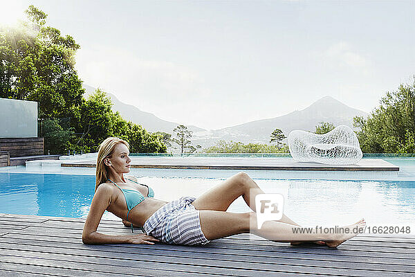 Young woman lying down near pool on sunny day