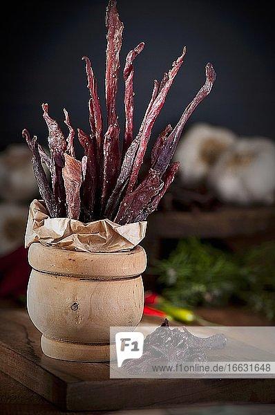 Dried pork jerky sticks in a wooden mortar