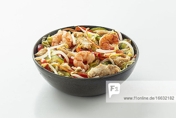 A bowl with shrimps  chicken  soya sprouts and vegetables