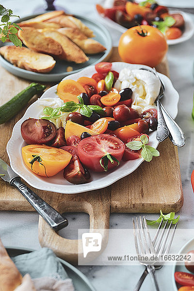 Caprese salad platter with tomatoes  mozzarella  basil  croutons and olives