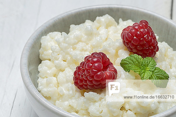 A bowl of rice pudding garnished with raspberries