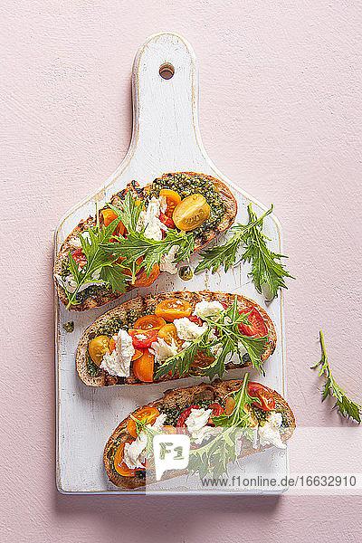 Grilled ciabbatta bread with pesto  mozzarella cheese  tomatoes and rocket salad