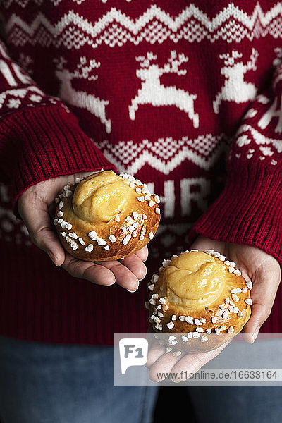 Crop female in red christmas sweater and jeans holding homemade tasty fresh buns with white sprinkles