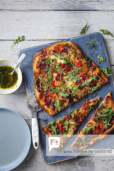 Homemade pizza with salami  mozzarella  sweet peppers  rocket and basil garlic oil