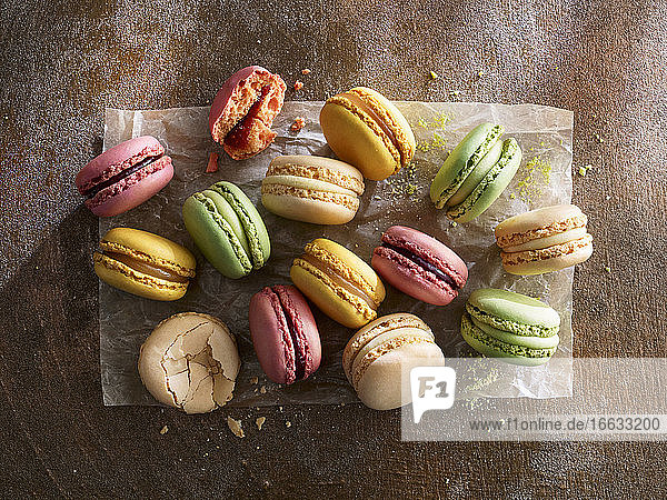 Different colorful macarons on paper against a wooden background