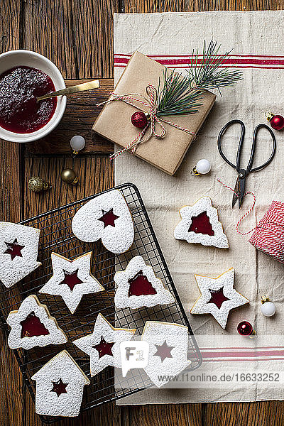 Homemade cookies of various shapes with red berry jam and white sugar powder for Christmas