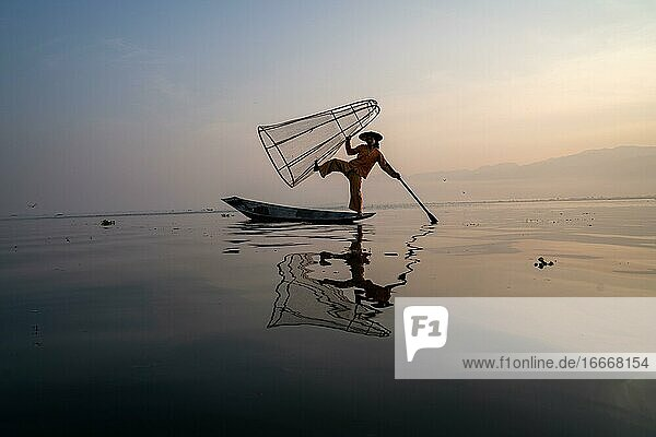 Traditional fisherman posing standing on his small boat with reflection in front of sunrise  Lake Inle  Myanmar  Asia