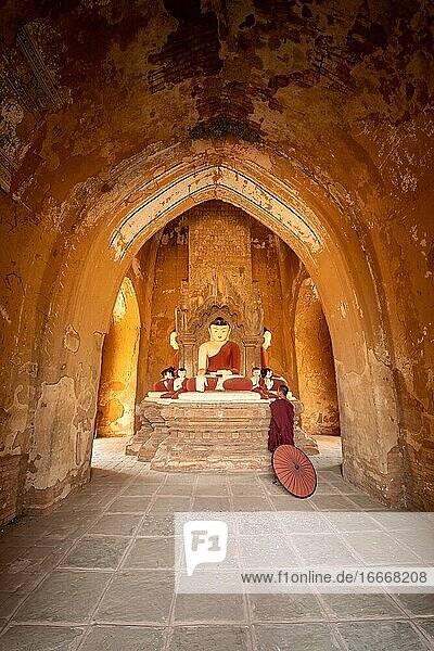 Buddhist young monk in red robe with red umbrella standing in a temple and praying  Bagan  Myanmar  Asia