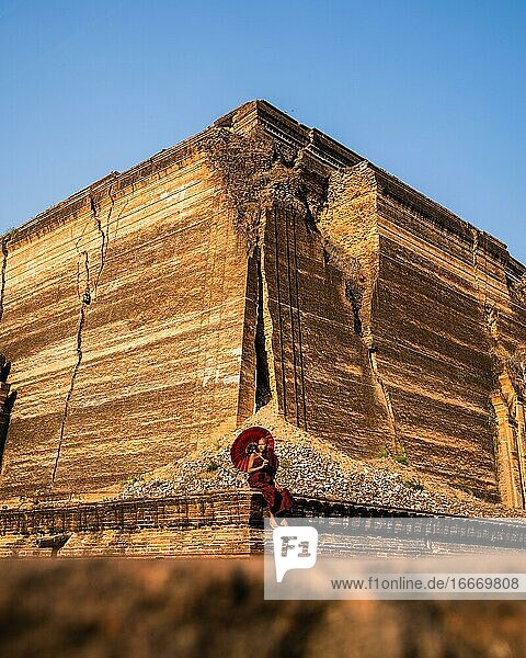 Buddhist monk sitting with red umbrella in front of Mingun Pagoda  Mingun  Myanmar  Asia