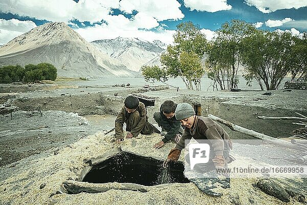 Three boys shovel wheat grains through the opening from above into a granary  members of the ethnic group of the sedentary Wakhi  Saradh-e-Broghil  Wakhan Corridor  Afghanistan  Asia