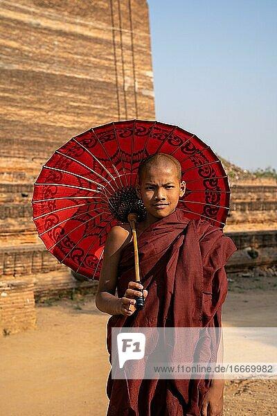 Buddhist monk stands with red umbrella in front of Mingun Pagoda  Mingun  Myanmar  Asia