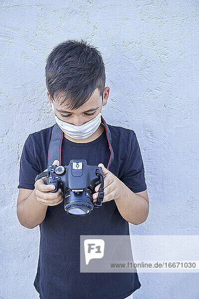 Little boy with his photography camera wearing a mask