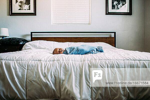Neugeborenes schläft allein auf großem Bett