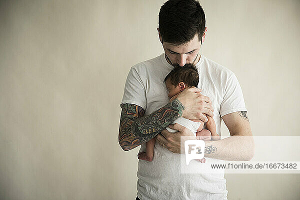 Tattooed Millennial Dad Kisses Top of Newborn Son's Head Tattooed Millennial Dad Kisses Top of Newborn Son's Head