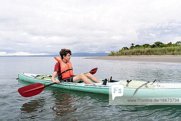 Teenager entspannt im Kajak in Costa Rica Teenager entspannt im Kajak in Costa Rica