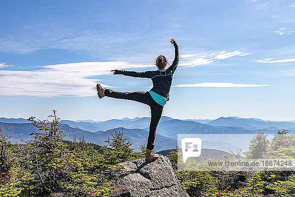 Young woman balancing on one leg at top of mountain.