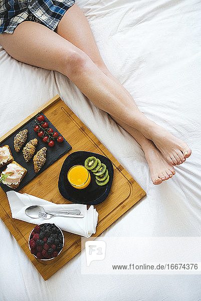 Close up of wome's legs and breakfast tray on bed in white bedroom.
