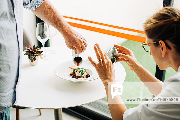 Woman taking photos of food with smartphone while waiter serving meal