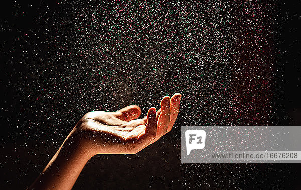 Hand reaching into a sparkling mist against a black background.