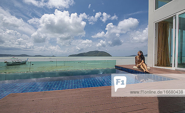 beautiful woman sitting by the pool at luxury villa in Phuket