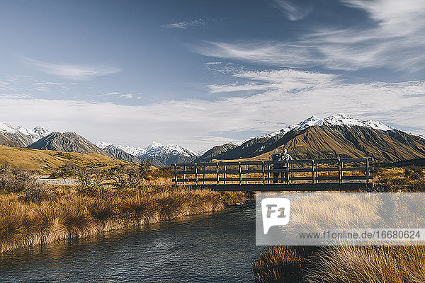 A couple stands in a bridge over a creek Lake Clearwater  Southern Alp
