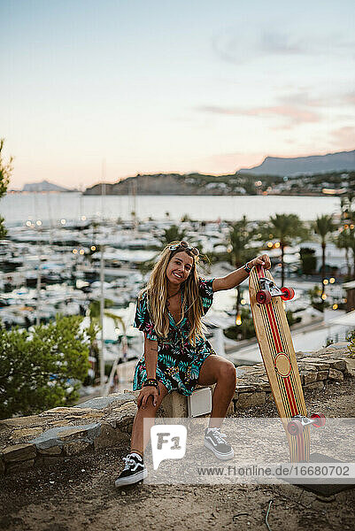 Young female with skate board in front of Moraira's yacht club at dusk