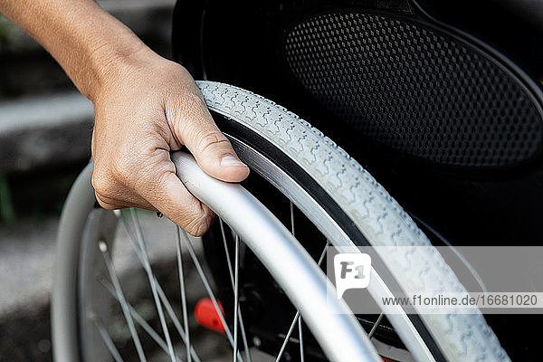 Close-up of a woman's hand on the wheel of a wheelchair. Concept of re