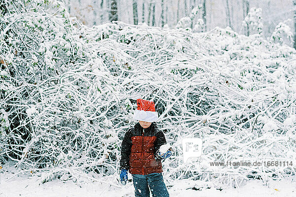 Little boy playing during a snowfall with his Santa hat on her head