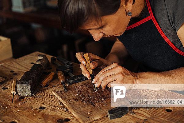 Frau beim Gravieren einer Holztafel mit Handwerkzeugen Frau beim Gravieren einer Holztafel mit Handwerkzeugen
