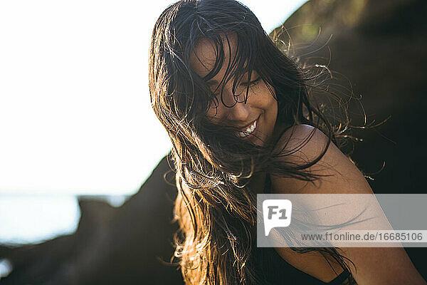 Junge Latina Frau lachend am Meer zur goldenen Stunde im Sommer Junge Latina Frau lachend am Meer zur goldenen Stunde im Sommer