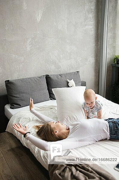 Adorable Frau spielt mit Kind auf dem Bett liegend  genießt Wochenende drinnen