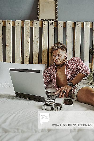 ein Mann arbeitet mit seinem Laptop in einem Hotelbett.