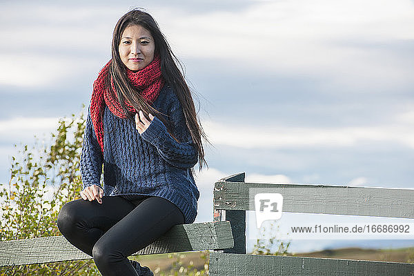 beautiful woman sitting on a fence at the Lake Myvatn area