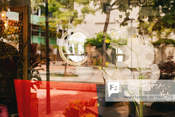 woman seen through glass while drinking coffee in a coffee shop