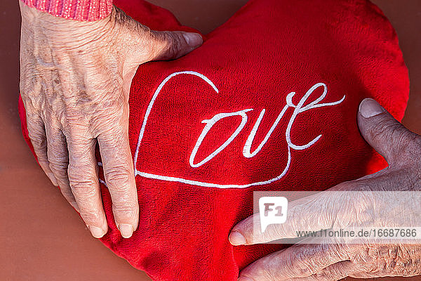 Elderly couple holding heart with Love word