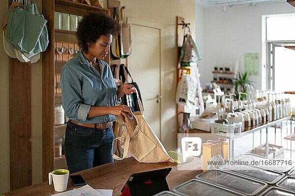 Afroamerikanische Frau packt Bestellung in wiederverwendbare Tasche Afroamerikanische Frau packt Bestellung in wiederverwendbare Tasche