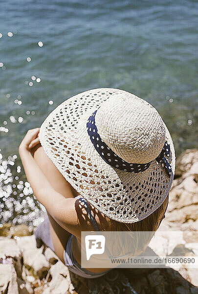 Woman with hat sitting on the beach by the sea