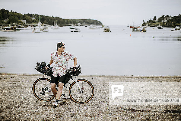 male cyclist takes break on beach in front of harbor  Harpswell  Maine