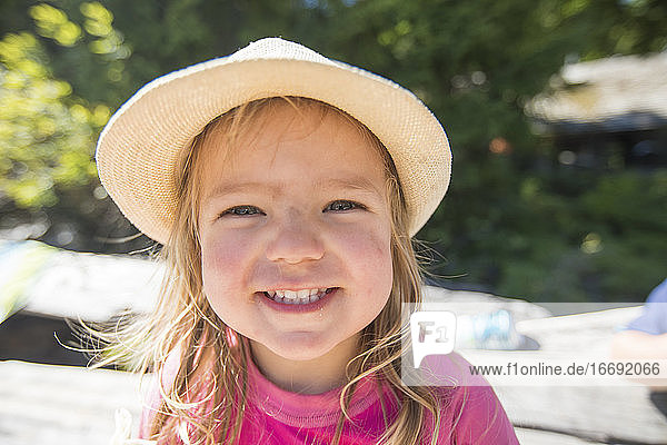 Portrait of cute young girl wearing sun hat at the beach