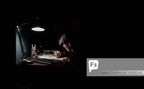 Teenage boy drawing at a desk in a dark room by lamp light.