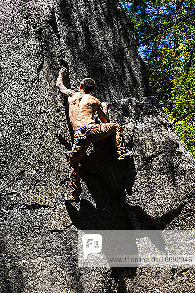Shirtless fit climber getting to the top of the boulder