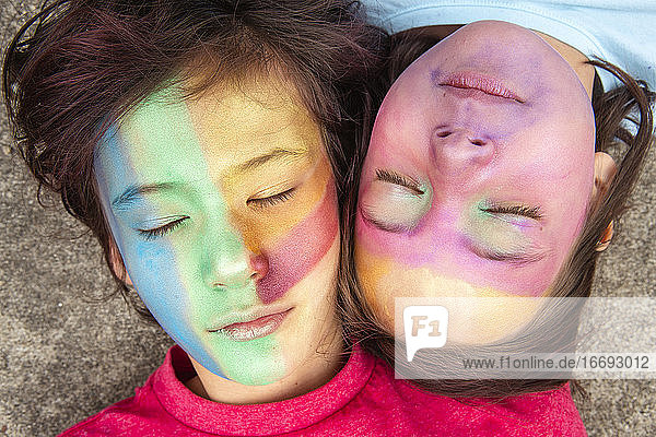 Two peaceful children in face paint lay together with eyes closed
