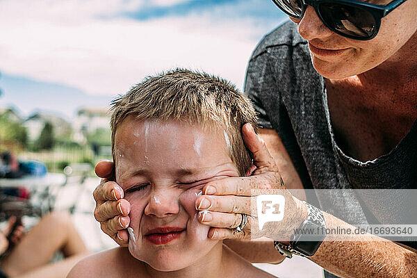 Nahaufnahme einer Mutter  die ihrem Sohn an einem Sommertag Lotion ins Gesicht schmiert Nahaufnahme einer Mutter, die ihrem Sohn an einem Sommertag Lotion ins Gesicht schmiert