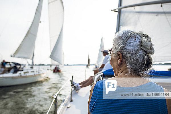 Frau mittleren Alters genießt die Sommer-Segelregatta während der goldenen Stunde Frau mittleren Alters genießt die Sommer-Segelregatta während der goldenen Stunde