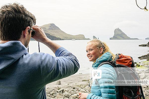 Fröhliche junge Reisende am Meeresufer