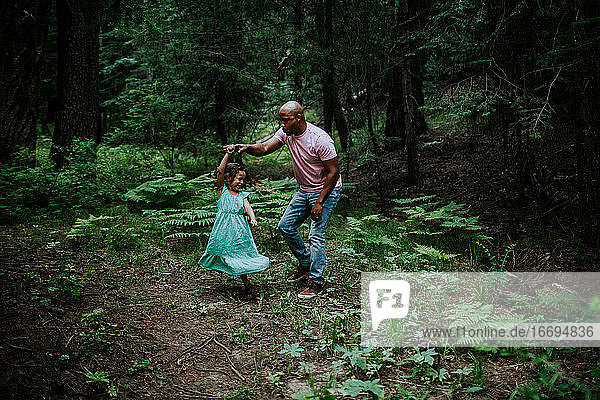 Father and daughter dancing in the middle of the forest