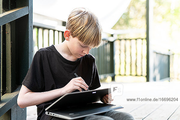 Tween sitting outside on porch using touch screen tablet with stylus