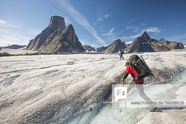 Mountaineer crosses a river on the Caribou Glacier  Baffin Island